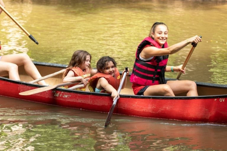 children canoeing with counselor at riverbend