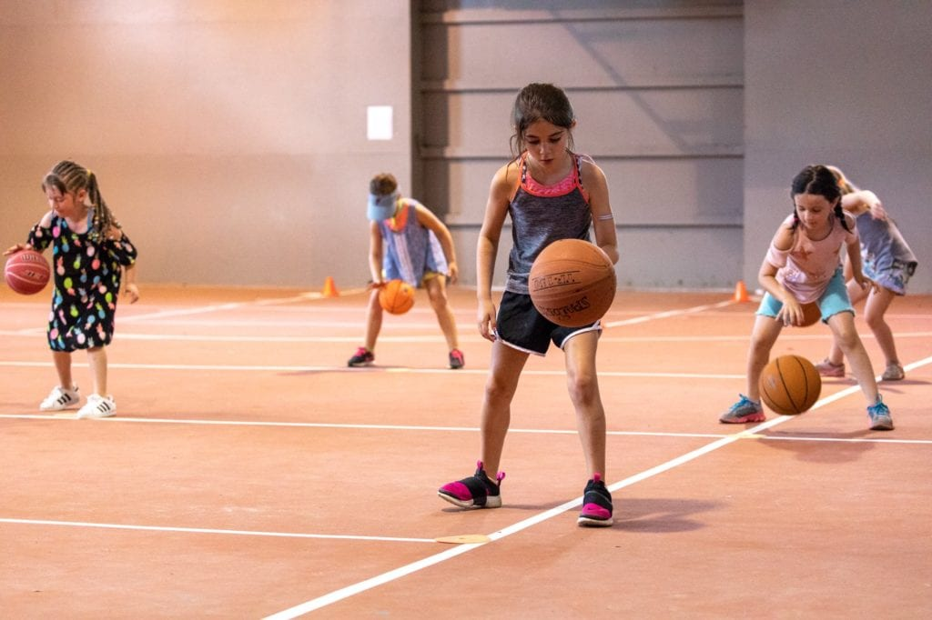 girls learning basketball dribbling